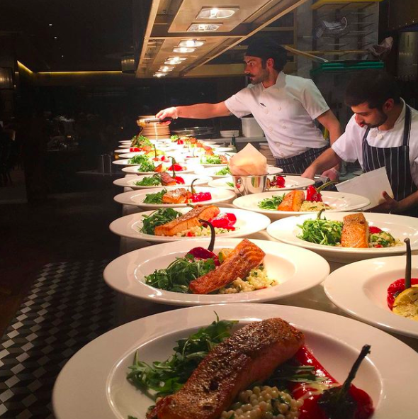 Chefs preparing fine dining dishes in the kitchen at Six at The Varsity